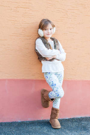 earmuff: Cute little girl posing outdoors, wearing white blouse, faux fur vest, white printed jeans and earmuff