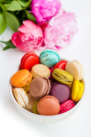 Colorful macaroons in a bowl with peonies on a white background Фото со стока
