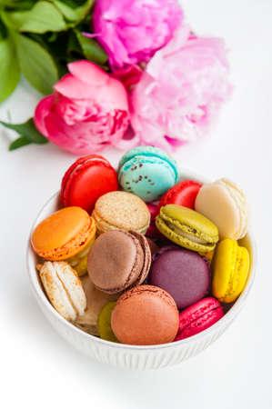 Kleurrijke bitterkoekjes in een kom met pioenrozen op een witte achtergrond