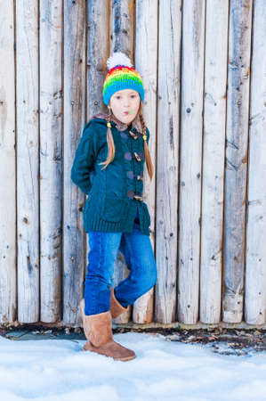 brigt: Winter portrait of a cute little girl, standing next to wooden wall, wearing, green cardigan, jeans, brown boots and colorful hat Stock Photo