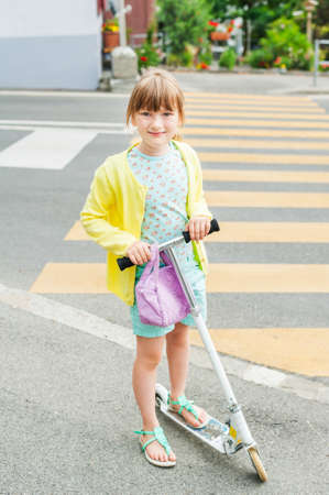 cross street with care: Pretty little girl is going to cross the road alone Stock Photo