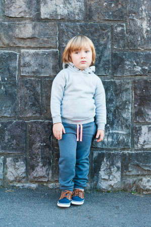 beautiful sad: Outdoor portrait of a cute little boy against stone wall