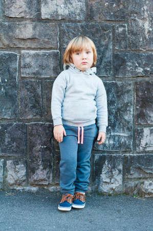 sad boy: Outdoor portrait of a cute little boy against stone wall