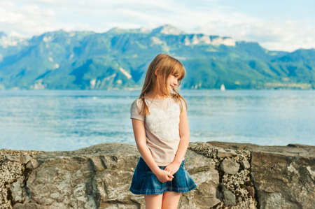Adorable little girl resting by the lake on a nice warm summer day Stock Photo