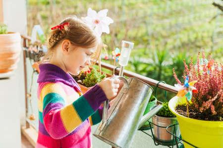 Schattig meisje planten water geven op het balkon op een mooie zonnige dag