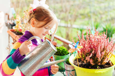 flower in pot: Adorable little girl watering plants on the balcony on a nice sunny day Stock Photo