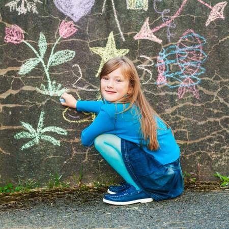 Leuk meisje plezier buitenshuis, tekening met een krijt op de muur, gekleed in een blauwe trui en panty's