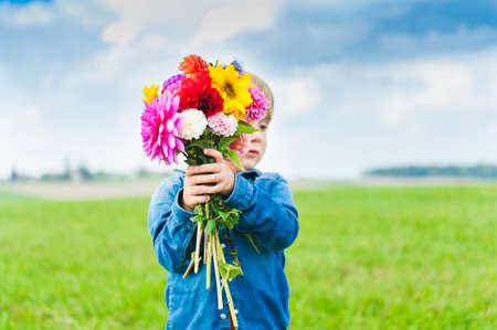 Beautiful bouquet of bright and colorful flowers holding by cute toddler boy