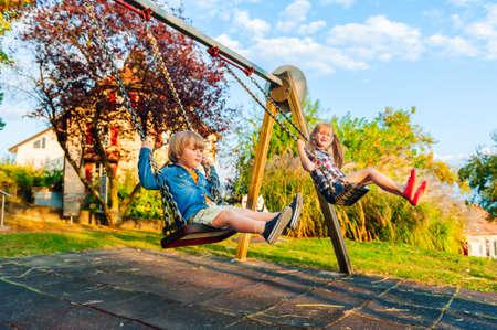 Schattige kinderen plezier buitenshuis op zonsondergang, spelen op een schommel