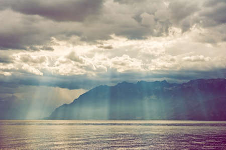 judgement day: Beautiful sun rays falling through heavy clouds on the mountains and the lake.  Color toned image. Stock Photo