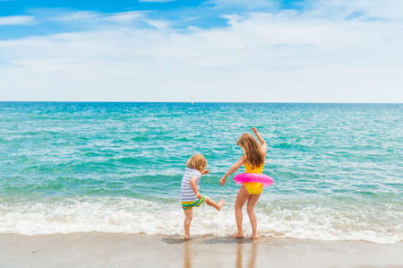 child on beach: Two kids having fun on summer vacation, playing in the sea