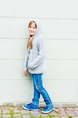 7 8 years: Outdoor portrait of a cute little girl wearing grey knitted parka, jeans and blue shoes