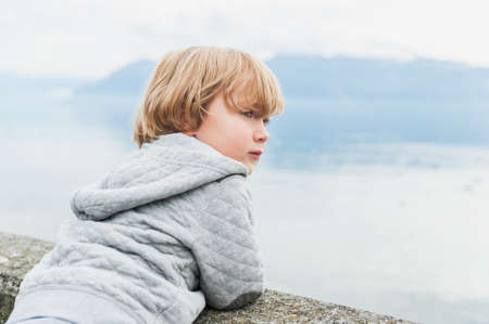 cabello rubio: Muchacho adorable del niño que descansa por el lago en un día fresco Foto de archivo