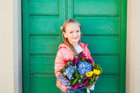7 8 years: Portrait of adorable little girl on a street in a city, holding beautiful bouquet of autumn flowers