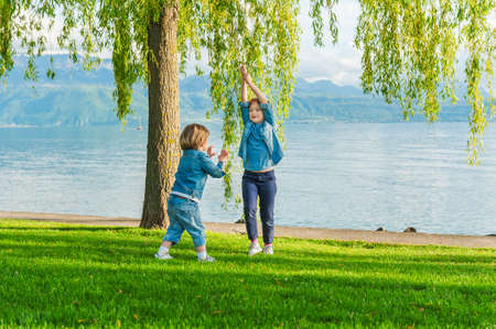 Two kids having fun outdoors on a nice sunny day, playing by the lake photo