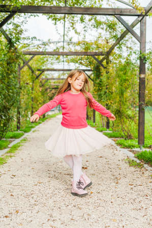 innocent girl: Cute little girl spinning around in a beautiful park, wearing tutu skirt, pink pullover and boots Stock Photo