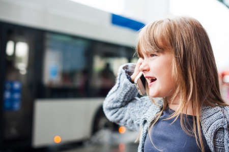 7 8 years: Little girl talking on a phone in a city Stock Photo