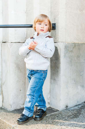 3 4 years: Outdoor portrait of a cute toddler boy, wearing grey pullover, jeans and black boots Stock Photo