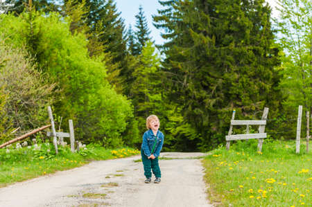 Cute toddler boy standing in the middle of the forest road and screaming Archivio Fotografico