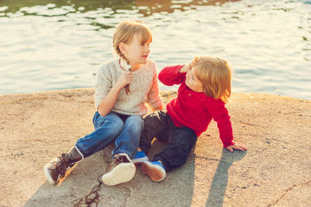 Two kids, little girl and boy resting by the lake on sunset, wearing pullovers and jeans, toned image photo