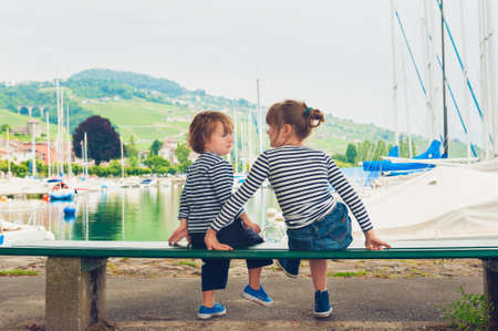 little girl sitting: Two kids, little girl and boy resting by the lake, wearing frocks and blue shoes
