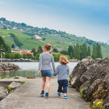 Two kids, brother and sister walking by the lake, wearing frocks and blue shoes, back view photo