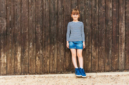 denim skirt: Outdoor portrait of a cute little girl, wearing frock, denim skirt and beautiful blue sneakers, standing against brown wooden wall Stock Photo