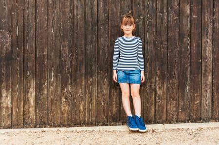 faldas: Retrato al aire libre de una niña linda, vestido vestido, falda vaquera y hermosas zapatillas azules, de pie contra la pared de madera marrón
