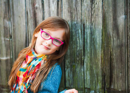 Outdoor portrait of a cute little girl in glasses, toned image