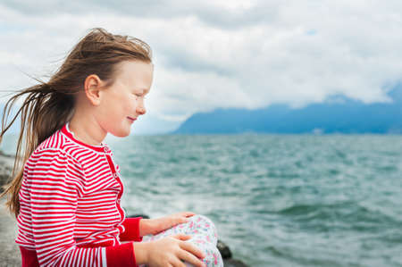 very windy: Adorable little girl resting by the lake on a very windy day