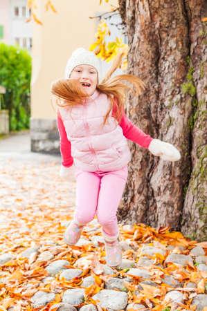 folliage: Adorable little girl having fun outdoors on a nice autumn day