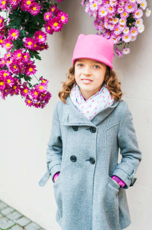 pink hat: Outdoor portrait of a cute little girl, wearing grey coat and pink hat