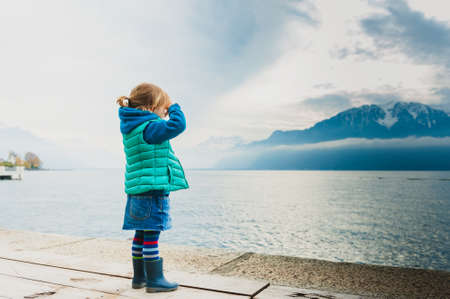 jeans skirt: Adorable toddler girl playing by the lake, looking at the mountains, wearing, rain boots, jeans skirt and green waistcoat Stock Photo