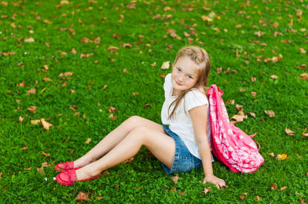 red grass: Little girl resting in a park after school