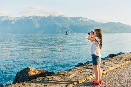 faldas: La niña linda de pie junto a hermoso lago en la puesta del sol y mirando con binoculares Foto de archivo