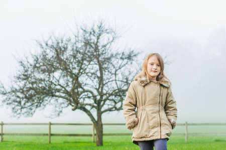 mistery: Outdoor portrait of a cute little girl in a garden on a foggy day, wearing warm beige coat Stock Photo
