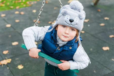 enfant qui joue: Adorable bébé garçon jouant sur une aire de jeux sur une journée froide, porter drôle de chapeau Banque d'images