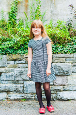 6 7 years: Outdoor portrait of a cute little girl, wearing dress and red shoes Stock Photo