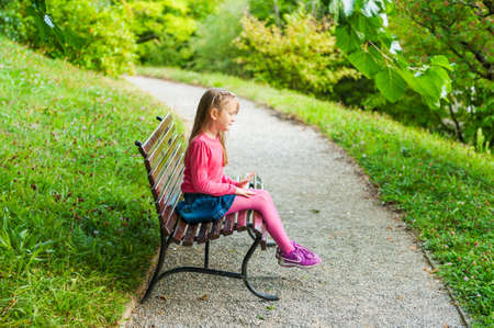 pretty little girl: Cute little girl playing in a park, sitting on a bench on a nice sunny day, outdoors