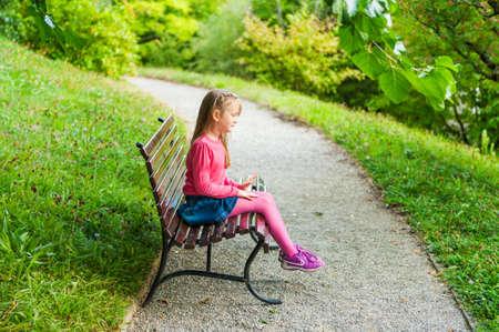 Het leuke meisje spelen in een park, zittend op een bankje op een mooie zonnige dag, in openlucht Stockfoto