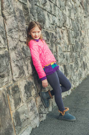 Outdoor portrait of a cute little girl on the street, wearing bright pink coat, grey leggins and blue boots, toned image Foto de archivo