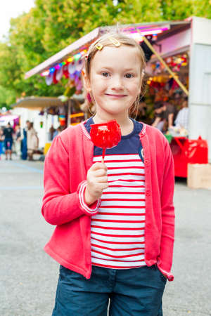 candy apple: Adorable little girl with candy apple at the fair