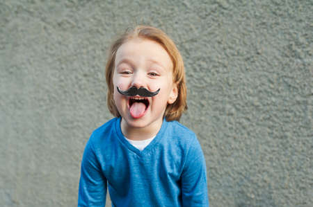 silly face: Outdoor close up portrait of a cute little boy with fake moustache, showing a tongue. Little einstein style