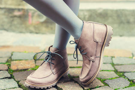 feet up: Close up of beige boots on feet of the child Stock Photo