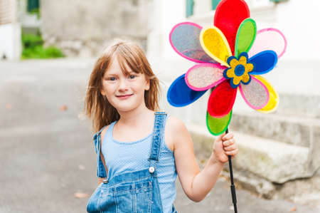 Cute little girl playing with pinwheel outdoors photo