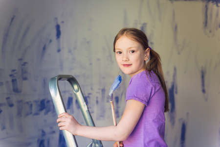 step ladder: Cute little girl sitting on a step ladder, holding a brush. Renovation concept Stock Photo