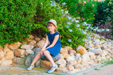 Outdoor portrait of a cute little girl of 6 years old in a beautiful garden, wearing blue dress, shoes and hat photo