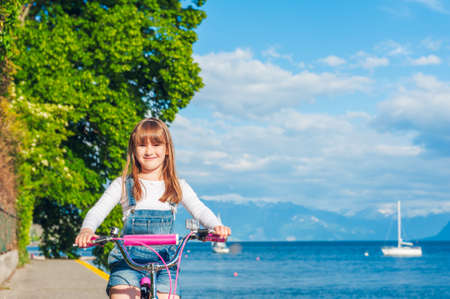 Cute little girl riding on a bicycle by the lake photo