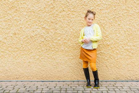 skirts: Moda retrato de una linda niña de 7 años de edad, llevaba blusa, chaqueta amarilla, falda naranja y botas de lluvia negras Foto de archivo