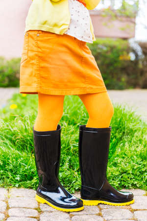 tights: Black rain boots on the feet of the child Stock Photo